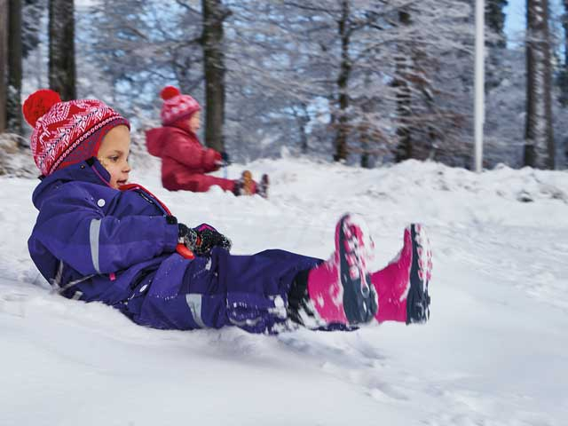 Rodelnde Kinder im Winter